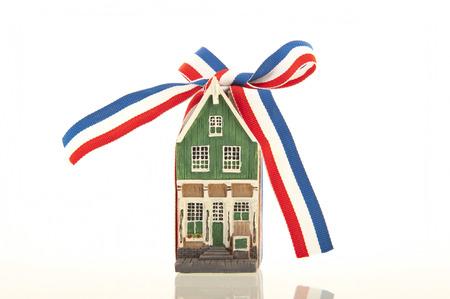 canal house: Vecchia casa sul canale olandese con un nastro rosso-bianco-blu annodato in un fiocco isolato su uno sfondo bianco