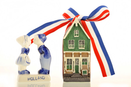 dutch canal house: Old Dutch canal house with a red-white-blue ribbon knotted in a bow next to kissing old Dutch farm kids Stock Photo