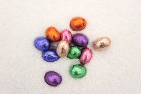 easteregg: Colored chocolate Easter eggs in a snowy white background