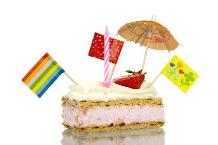 Pastry treat with sweet glaze and whipped cream topping filled with creamy strawberry filling, decorated with a candle, flags, umbrellas and puppets isolated on white background photo