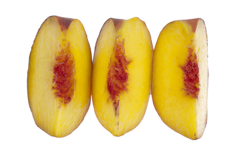 Half a peach cut in three parts ornate in a row and isolated in white background photo
