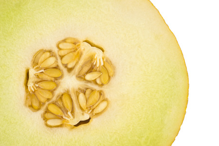 A sliced yellow melon with core in closeup and  isolated in white photo