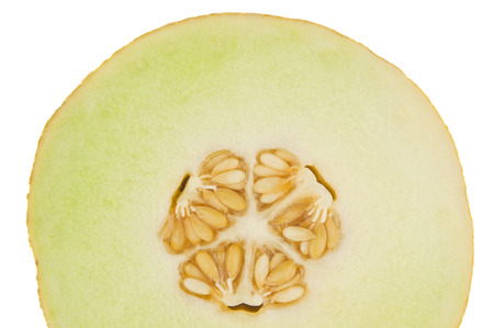 A yellow melon cut across with three sections core isolated in white photo