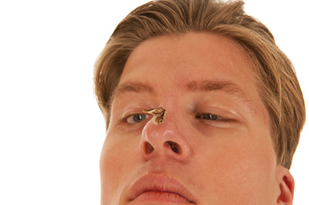 Boy looking confused and squint-eyed at a moth sitting on his nose in closeup photo
