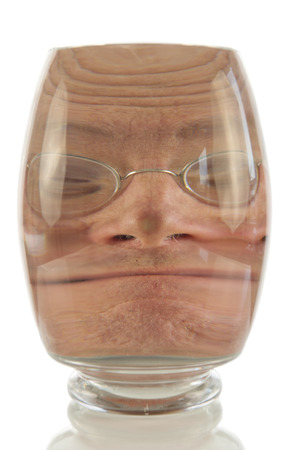 Crazy male face locked up in vacuum of glass bell photo