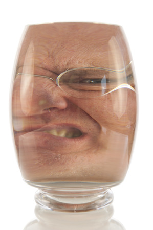 Angry male face locked up in vacuum of glass bell photo