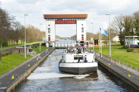 sluice: Sluice complex with water filled reservoir and passing cargo ship on april 9, 2010 in the Twente channel at Eefde, the Netherlands