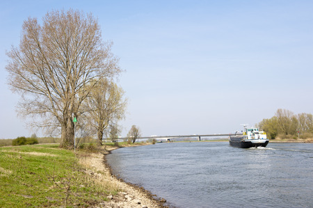 downstream: Cargo boat navigating downstream in a rural scenery on the river IJssel on april 13, 2010 at Wilp, the Netherlands