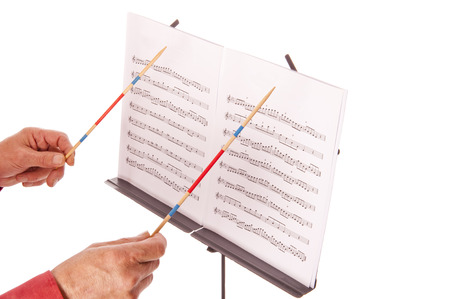 conducting: Conductor with baton directing melody from music sheet stand  Stock Photo