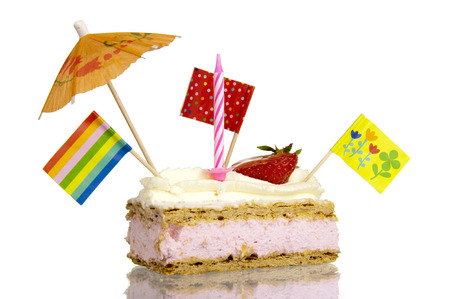 Pastry treat with sweet glaze and whipped cream topping filled with creamy strawberry filling, decorated with candles, flags, umbrellas and puppets  photo