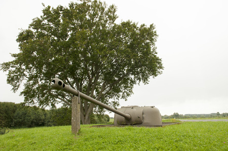 Historic second world war cannon buried in ground photo