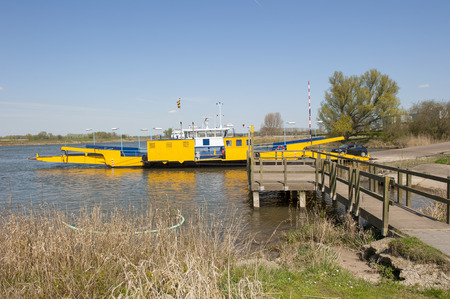 landing stage: Yellow ferry in river landscape docked at landing stage on levee