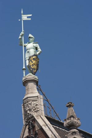 Knight with shining armor standing proud with pylon and shield on top of a building near the Central Train Station in Amsterdam taken from the side photo