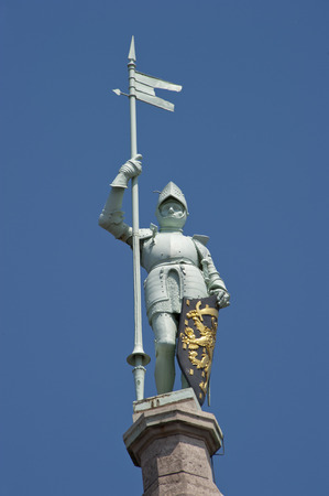 Knight with shining armor standing proud with pylon and shield on top of a building near the Central Train Station in Amsterdam taken in close up photo
