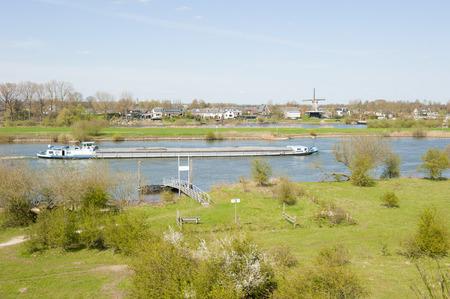 ijssel: Cargo ship on river IJssel passing quay of ferry in rural landscape at Veessen, the Netherlands