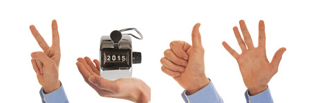 Male hands with analog pedometer display picturing the year 2015 photo