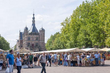 DEVENTER, THE NETHERLANDS - AUGUST 3, 2014  The Deventer book market in the Netherlands on august 3, 2014   The Brink  plaza crowded with people with the famous and historic building  the Waag  in the background