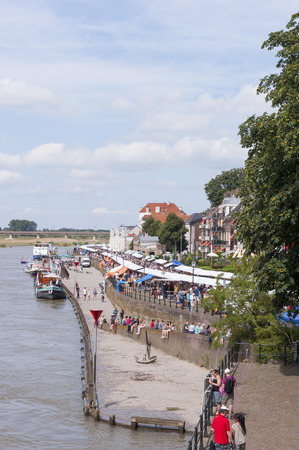DEVENTER, THE NETHERLANDS - AUGUST 3, 2014  The Deventer book market in the Netherlands on august 3, 2014  A long stripe of book stalls crowded with people along the riverwalk