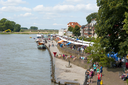 ijssel: DEVENTER, THE NETHERLANDS - AUGUST 3, 2014: Crowded boulevard of the river IJssel as shopping people gather around the book stalls. The Deventer bookmarket is an annual event and visited bij over 125.000 visitors.