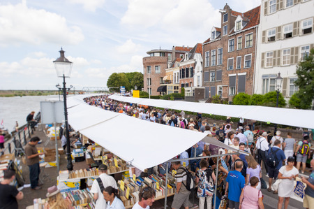 DEVENTER, THE NETHERLANDS - AUGUST 3, 2014. A long queue of market stalls with shopping people at the annual Deventer book market in the Netherlands on august 3, 2014. The book stands filled with second hand books along the boulevard of the river IJssel c