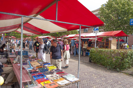 DEVENTER, THE NETHERLANDS - AUGUST 3, 2014. Market stalls of famous and historic book fair with shopping people at the Deventer book market in the Netherlands on august 3, 2014. The red white colored book stands filled with second hand books and crowded w