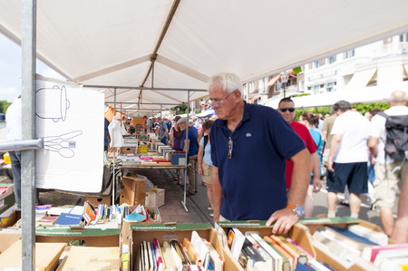 DEVENTER, THE NETHERLANDS - AUGUST 3, 2014. People shop at the Deventer book market in the Netherlands on august 3, 2014. The book stand loaded with second hand books and the promenade crowded with people looking around the book stalls. Focal point is til