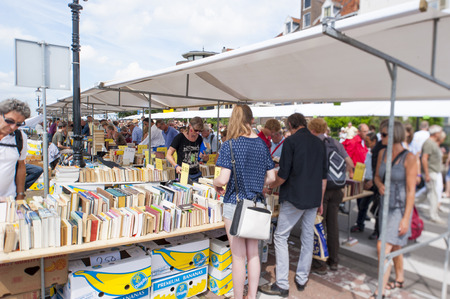 DEVENTER, THE NETHERLANDS - AUGUST 3, 2014. People shopping at the Deventer book market in the Netherlands on august 3, 2014. The book stands filled with second hand books and the promenade crowded with people looking around the book stalls. Focal point i