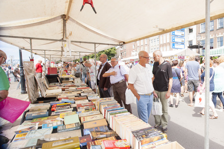 DEVENTER, THE NETHERLANDS - AUGUST 3, 2014. Men looking for sales at the book stands filled with second hand books. The promenade crowded with people looking around the book stalls. The Deventer bookmarket is an annual event and visited bij over 125.000 v