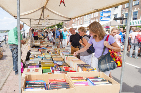 DEVENTER, THE NETHERLANDS - AUGUST 3, 2014. People looking around in the second hand book stalls. The book stands filled with books and the promenade crowded with shopping people looking around. The Deventer bookmarket is an annual event and visited bij o
