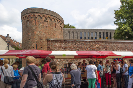 DEVENTER, THE NETHERLANDS - AUGUST 3, 2014. Shopping pedestrians looking around the book stands at the Deventer book market in the Netherlands on august 3, 2014. The Deventer market fair is located in the historic town center and is an annual event that i
