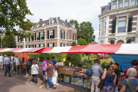 DEVENTER, THE NETHERLANDS - AUGUST 3, 2014. Market stalls of famous and historic book fair with shopping people at the Deventer book market in the Netherlands on august 3, 2014. The book stands filled with second hand books crowded with shopping people lo