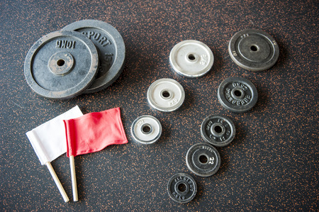 Set of dumbbell weight plates with red and white referee flags arranged on black floor photo