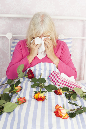 heartbreak issues: Sad woman in pink pyjama sitting in bed with a bunch of roses and tissues