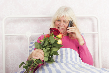 pyjama: Happy woman in pink pyjama sitting in bed with roses and talking on the phone