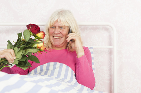 pyjama: Smiling female in pink pyjama sitting in bed with a bunch of roses and talking on the phone