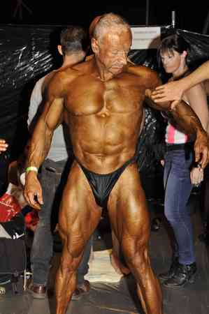nether: ROOSENDAAL, THE NETHERLANDS - OCTOBER 19, 2014. Male bodybuilding contestant gets his tan in preperation of his contest at the Walters Open Dutch Championship Bodybuilding and Fitness on oktober 19, 2014 in Theatre De Kring at Roosendahl, the Nether