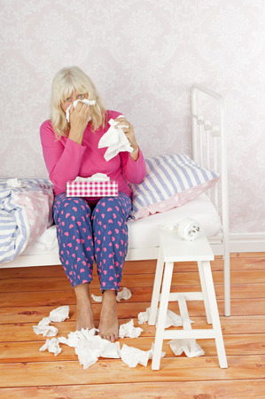 heartbreak issues: Sick female with pink pajama and tissues sitting on bed Stock Photo
