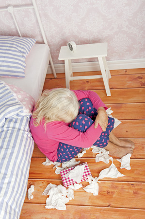 heartbreak issues: Sad woman with pink pajama and tissues sitting on floor against bed Stock Photo