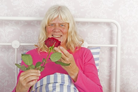 in pajama: Smiling female in pink pajama sitting in bed with a red rose