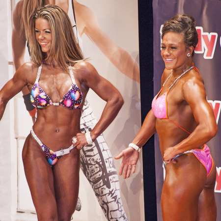 schiedam: Female bikini models smile to the crowd at the 38th Dutch National Championship Bodybuilding and Fitness of the IFBB Netherlands (NBBF) on april 26, 2015 in Theatre aan de Schie at Schiedam, the Netherlands. Winning this A rated Championship leads to