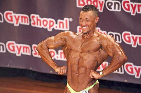 schiedam: Male bodybuilder showing his best lats spread pose at the 38th Dutch National Championship Bodybuilding and Fitness of the IFBB Netherlands (NBBF) on april 26, 2015 in Theatre aan de Schie at Schiedam, the Netherlands. Winning this A rated Championshi