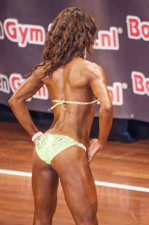 schiedam: Female bikini model showing her best back pose at the 38th Dutch National Championship Bodybuilding and Fitness of the IFBB Netherlands (NBBF) on april 26, 2015 in Theatre aan de Schie at Schiedam, the Netherlands. Winning this A rated Championship le