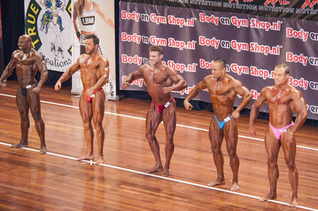 schiedam: Male bodybuilders showing their best in a comparison lineup at the 38th Dutch National Championship Bodybuilding and Fitness of the IFBB Netherlands (NBBF) on april 26, 2015 in Theatre aan de Schie at Schiedam, the Netherlands. Winning this A rated Ch