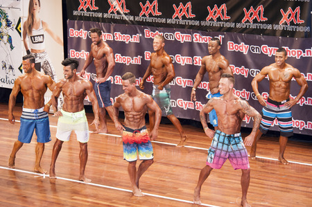 schiedam: Male fitness contestants showing their best in a lineup comparison at the 38th Dutch National Championship Bodybuilding and Fitness of the IFBB Netherlands (NBBF) on april 26, 2015 in Theatre aan de Schie at Schiedam, the Netherlands. Winning this A r Editorial