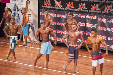 schiedam: Male fitness contestants show their physique in a lineup comparison at the 38th Dutch National Championship Bodybuilding and Fitness of the IFBB Netherlands (NBBF) on april 26, 2015 in Theatre aan de Schie at Schiedam, the Netherlands. Winning this A  Editorial
