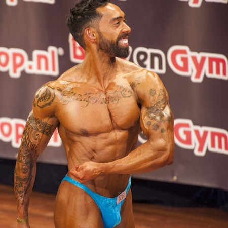 schiedam: Male bodybuilder showing his best at the 38th Dutch National Championship Bodybuilding and Fitness of the IFBB Netherlands (NBBF) on april 26, 2015 in Theatre aan de Schie at Schiedam, the Netherlands. Winning this A rated Championship leads to qualif