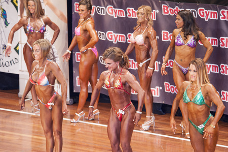 schiedam: Female bikini models smile to the public in a comparison lineup at the 38th Dutch National Championship Bodybuilding and Fitness of the IFBB Netherlands (NBBF) on april 26, 2015 in Theatre aan de Schie at Schiedam, the Netherlands. Winning this A rate