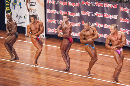 schiedam: Male bodybuilders showing their best in a lineup at the 38th Dutch National Championship Bodybuilding and Fitness of the IFBB Netherlands (NBBF) on april 26, 2015 in Theatre aan de Schie at Schiedam, the Netherlands. Winning this A rated Championship