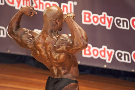 national championship: Male bodybuilders showing his best back double biceps pose at the 38th Dutch National Championship Bodybuilding and Fitness of the IFBB Netherlands (NBBF) on april 26, 2015 in Theatre aan de Schie at Schiedam, the Netherlands. Winning this A rated Cha