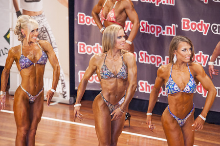 national championship: SCHIEDAM, THE NETHERLANDS - APRIL 26, 2015: Female bikini models showing their best at the 38th Dutch National Championship Bodybuilding and Fitness of the IFBB Netherlands (NBBF) on april 26, 2015 in Theatre aan de Schie at Schiedam, the Netherlands.